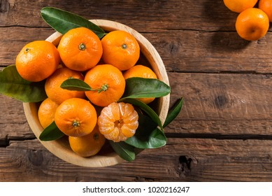 Delicious and beautiful mini Tangerines with leaves in the wooden bowl