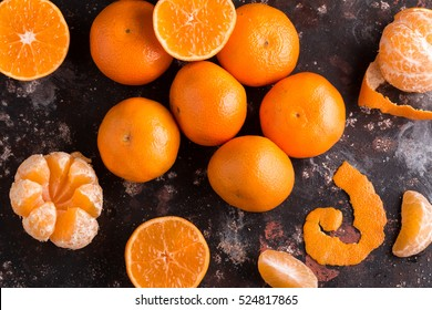 Delicious and beautiful Tangerines. Peeled Tangerine orange  and Tangerine orange slices on a Dark Background. Citrus background,  Top view.