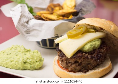 Delicious beef burger with plantain chips and guacamole on a new