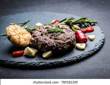 Delicious beef burger steak with spices and ingredients for cooking on slate background