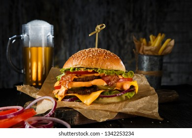 Delicious beef cheeseburger with  glass of beer , vegetables and lettuce, hand made, according to a classic recipe.