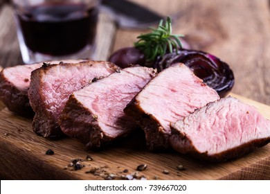 Delicious beef filet mignon served on wooden cutting board with roasted red onion and rosemary