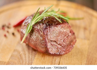 Delicious beef steak on wooden platter. Grilled beef steak with rosemary on wooden board.