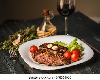 Delicious Beef steak with rosemary and thyme, lettuce, cherry tomatoes and red wine.