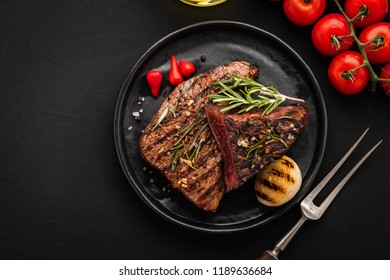Delicious beef steak with salad, aromatic herbs, chery tomatoes.