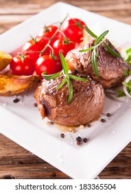 Delicious beef steaks with fresh vegetable and trimmings on wooden table.