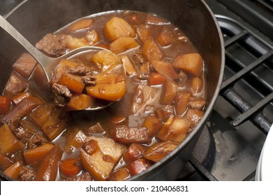 Delicious beef stew cooking in a pot in a rich gravy with potatoes and carrots for a traditional Lancashire Hotpot