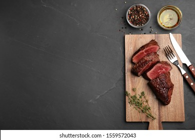 Delicious beef tenderloin served on black table. Space for text