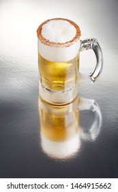 Delicious big mug of lagger beer rimmed with salt and bird's beak chili pepper, with a little foam, on a textured surface with a great reflection
