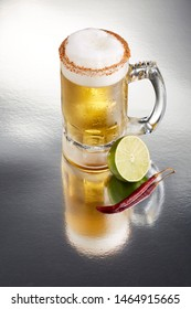 Delicious big mug of lagger beer rimmed with salt and bird's beak chili pepper, with a little foam, by half a lime and a full dry chili pepper on a textured surface with a great reflection