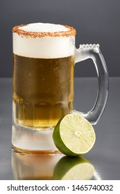 Delicious big mug of lagger beer rimmed with salt and bird's beak chili pepper, with a little foam, by half a lime on a dark background with a great reflection