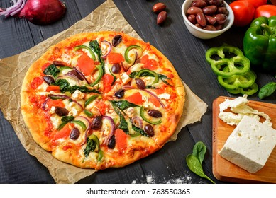 Delicious big vegan pizza with Mozzarella cheese, Kalamata black olives, Red onions, Spinach and Green bell pepper on a dark wooden background