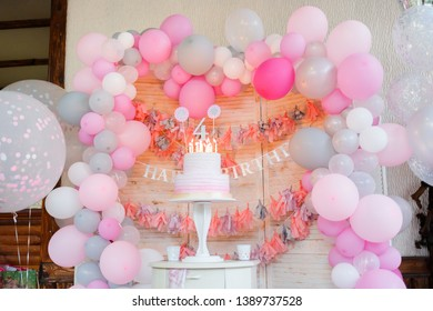 Delicious birthday cream cake with candles on the background with balloons. Beautiful cake with pink decoration for girl. Girl's birthday.