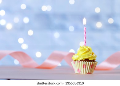 Delicious birthday cupcake with burning candle on wooden table against blurred lights