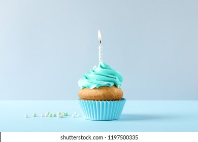 Delicious birthday cupcake with candle on light background