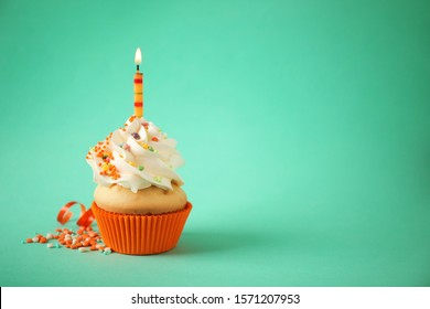 Delicious birthday cupcake with candle on light green background. Space for text