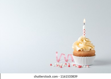 Delicious birthday cupcake with candle and space for text on gray background