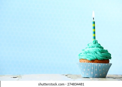 Delicious birthday cupcake on blue background