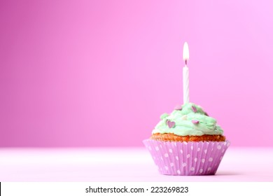 Delicious birthday cupcake on table on pink background
