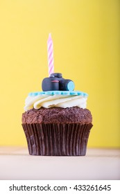 Delicious birthday cupcake with realistic camera icon on it and candle on wooden desk and yellow background