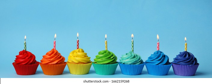 Delicious birthday cupcakes with burning candles on light blue background