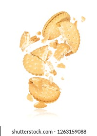Delicious biscuits crushed into pieces in the air, isolated on white background