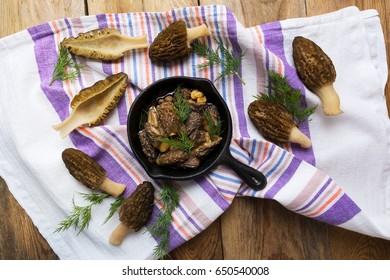 Delicious black morel mushrooms in skillet on rustic wooden table top view. Diet vegetarian food.