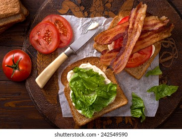 A delicious BLT bacon, lettuce, and tomato sandwich on rustic tabletop.
