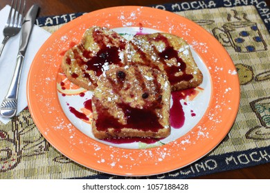Delicious Blueberry French Toast on a Citris Orange Plate with Silverware on a Placement