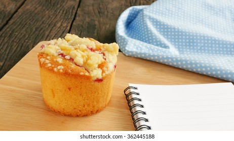 The delicious blueberry muffin and blue cotton fabric and small note book on the old deep brown planks.