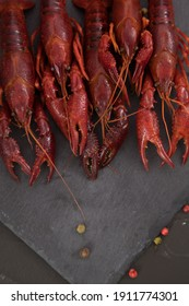 Delicious boiled crayfish close-up on a stone plate with pepper, lemon and parsley.