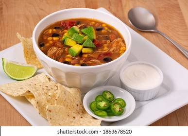 Delicious bowl of chicken taco soup garnished with avocado with sides of chili peppers, sour cream and tortilla chips