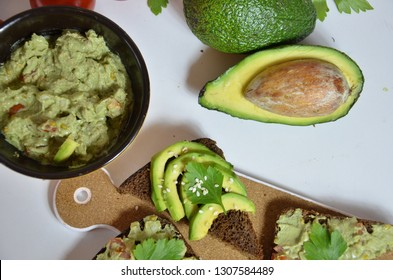 A delicious Bowl of Guacamole next to fresh ingredients on a table with tortilla chips and salsa. sandwich with guacamole, red hot pepper, lime, lemon, avocado.