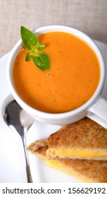 Delicious bowl of homemade tomato soup with a grilled cheese sandwich