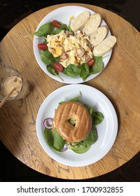 Delicious breakfast bagel and scrambled eggs served with a baguette served in a very stylish way