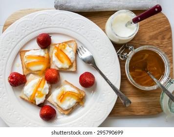 Delicious breakfast with bread, strawberries, yogurt and orange marmalade