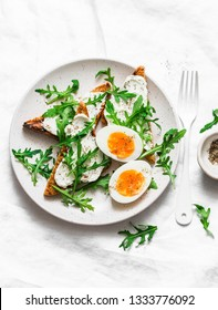 Delicious breakfast, brunch or snack - cream cheese toast, arugula salad and soft boiled egg on a light background, top view