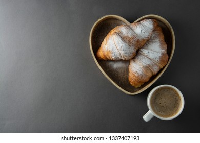 Delicious breakfast coffee with croissant. Heart shaped box. Morning caffeine. French, fresh pastry and cup of coffee or latte. Caffeine love.
