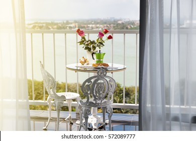 Delicious breakfast with coffee on hotel's balcony, decorated  with fresh roses, croissants and slice of orange fruit with coffee percolator background, overlooking sea view.