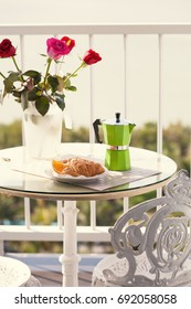 Delicious breakfast with coffee on hotel's balcony, fresh croissants and slice of orange fruit with coffee percolator background