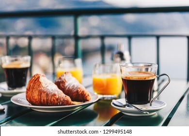 Delicious breakfast with coffee, pastry, and orange juice served on the balcony with sea view in Italy.