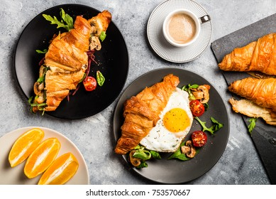 Delicious Breakfast with Croissant sandwiches with Fried Egg, Salad Leaves, Grilled Mushrooms and Cherry Tomatoes, Coffee and Orange Juice on Grey Background, Top View