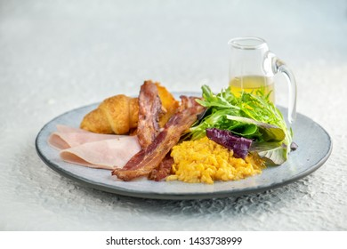 Delicious breakfast with eggs Scramble  omelette with little salad and juice, toasted, crispy bacon, English muffins, ham, poached eggs, and vinaigrette dressing sauce.wooden background . Top view
