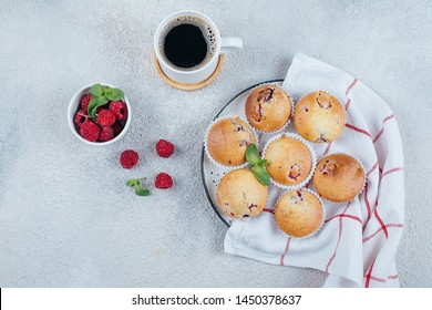 Delicious breakfast food concept. Coffee, raspberry muffins on light concrete background. Top view, flat lay