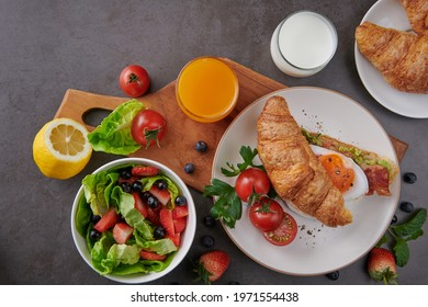 Delicious breakfast with fresh croissants, bacon sandwich with fried egg. milk served, orange juice. strawberry, butterhead, blackberry salad. full american healthy breakfast top view.