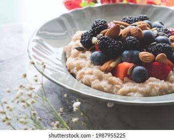 Délicieux petit-déjeuner, bouillie d'avoine sans gluten sur du lait de plante avec des amandes et des myrtilles, des fraises et des mûres sur une table en marbre