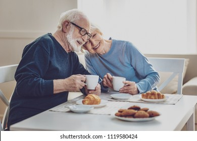 Delicious breakfast. Happy joyful couple smiling while having a meal together