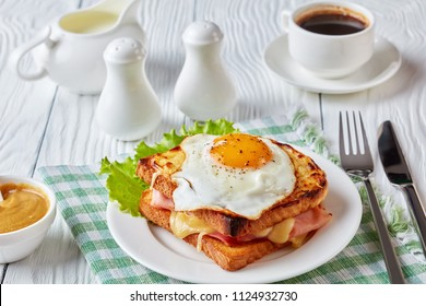 delicious breakfast - hot french toasts croque madame with ham, melted emmental cheese and fried sunny side up egg served on a white plate with cup of coffee on a table, view from above, close-up