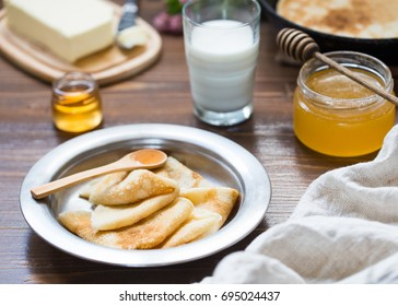 Delicious breakfast with pancakes, honey and milk