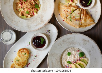 Delicious breakfast with pancakes and porridge
